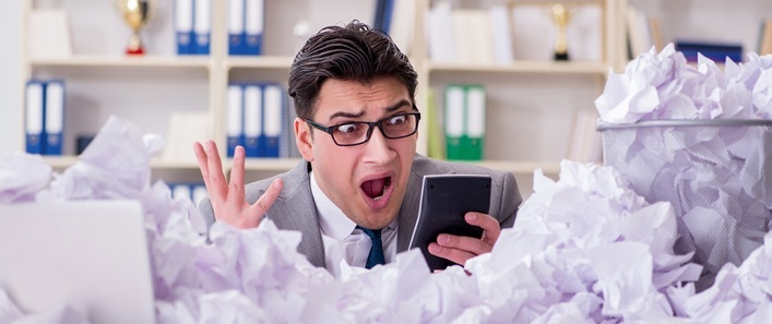 An accountant expresses shock as he holds a calculator above a pile of strewn papers.