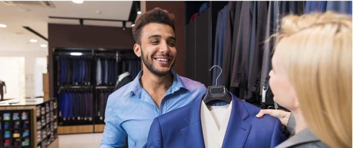 A store employee helps a man choose a suit to buy.