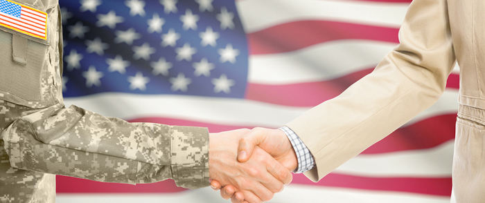 A military man and a business person shake hands.