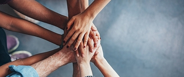 A group of hands clasp each other demonstrating teamwork.