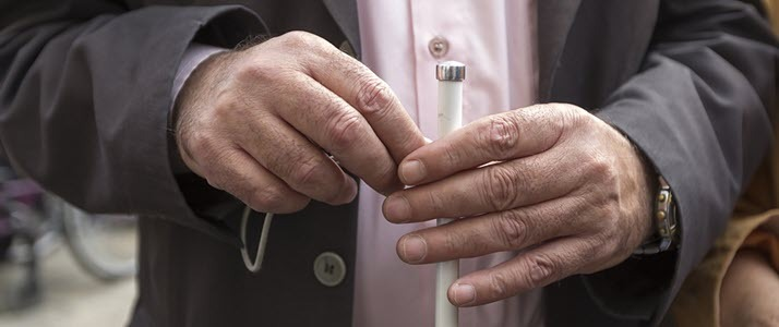 close up of blind mans hands with cane