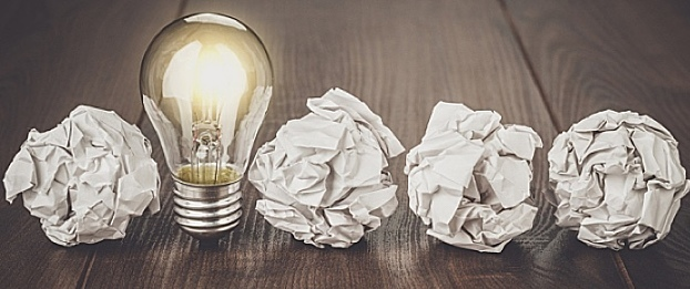 An image of a lightbulb, along with several pieces of crumpled paper, lined up on a table.