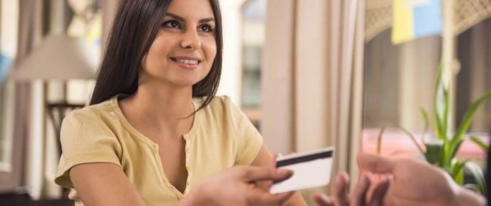 A woman pays at a store with a paycard