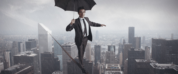 A businessman walks on tightrope between skyscrapers in the rain.