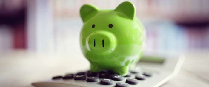 A green piggy bank sits on a calculator.