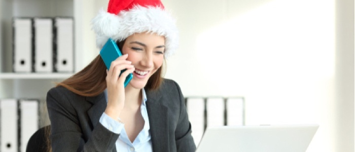 A business woman speaks on a cell phone while wearing a festive holiday hat.