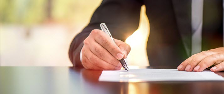man signing piece of paper on a desk