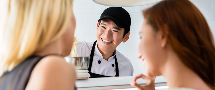 A smiling employee takes a customer's order.