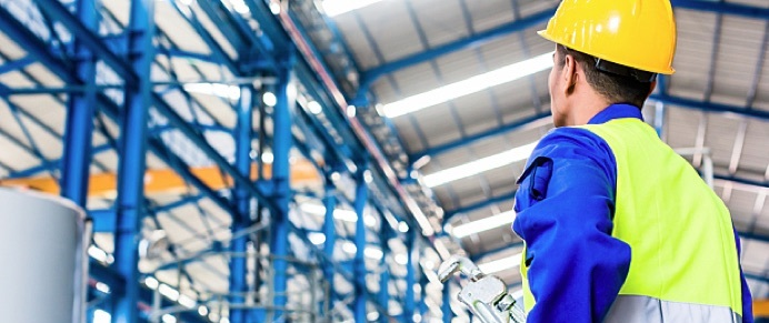 An industrial worker wearing a hard hat is in a factory.