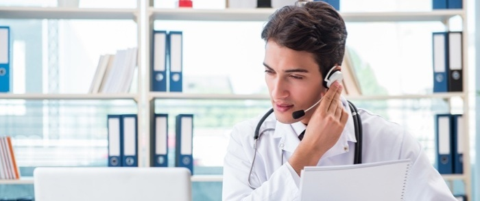 A young doctor works with telehealth and speaks on the phone.