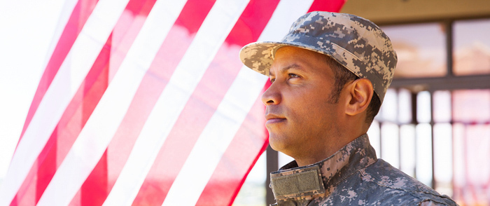 A man in military clothing stands near an American flag