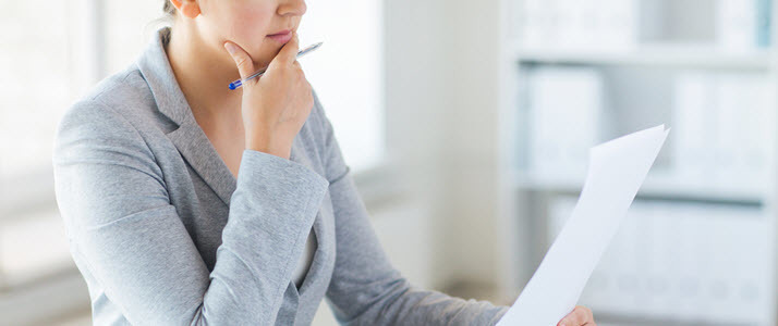 Woman at desk looks at piece of paper