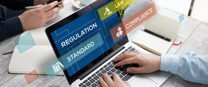The words regulation and compliance are shown on a laptop screen